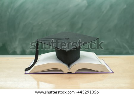 education concept,graduation cap above open book on classroom - stock photo