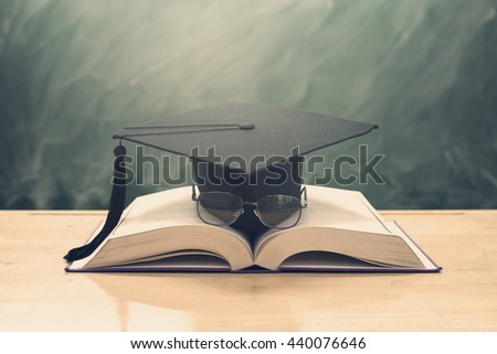 education concept,graduation cap and glasses above open book on classroom - stock photo