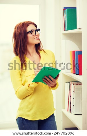 education concept - smiling redhead female student in eyeglasses with textbook in library - stock photo