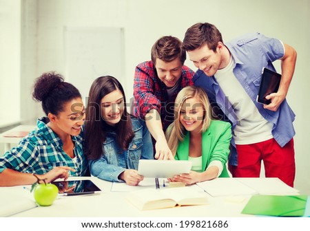 education concept - smiling students looking at tablet pc at school - stock photo