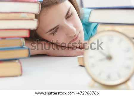 Education concept - tired student with pile of books and notes studying indoors.
