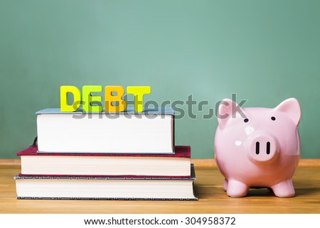 Education debt them with textbooks, piggy bank and chalkboard background - stock photo
