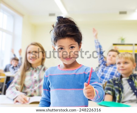 education, elementary school and children concept - happy little student with pen girl over classroom and classmates background - stock photo