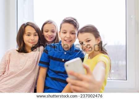 education, elementary school, drinks, children and people concept - group of school kids taking selfie with smartphone in corridor - stock photo