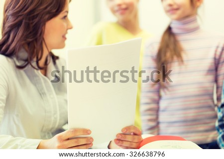 education, elementary school, learning and people concept - close up of school kids and teacher with papers talking in classroom - stock photo