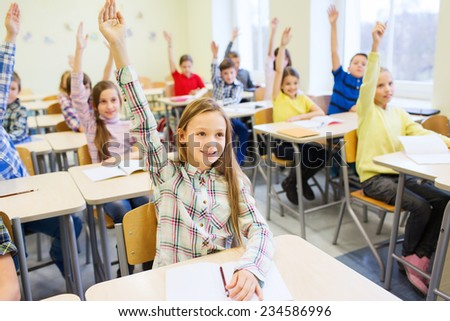 education, elementary school, learning and people concept - group of school kids with notebooks sitting in classroom and raising hands - stock photo