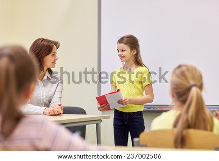 education, elementary school, learning and people concept - group of school kids with teacher talking in classroom - stock photo