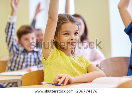 education, elementary school, learning and people concept - group of smiling school kids sitting in classroom - stock photo