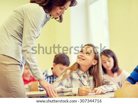 education, elementary school, learning and people concept - teacher helping school girl writing test in classroom - stock photo