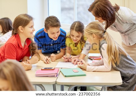 education, elementary school, learning and people concept - teacher helping school kids writing test in classroom - stock photo