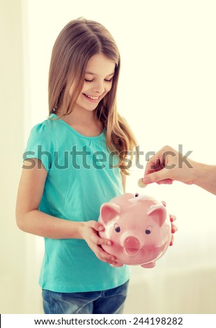 education, family, child and money saving concept - smiling little girl holding piggy bank and father putting coin into it - stock photo