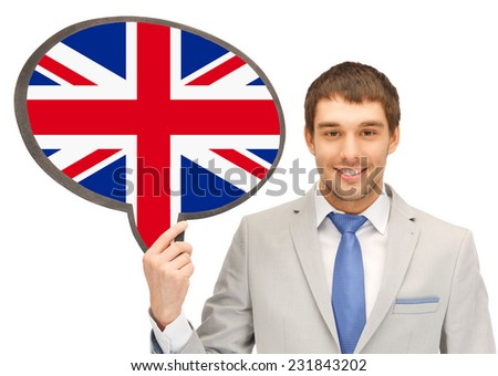 education, foreign language, english, people and communication concept - smiling young man or businessman in tie and suit holding text bubble of british flag - stock photo