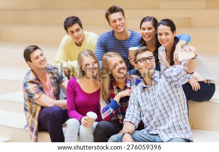 education, friendship, drinks, technology and people concept - group of smiling students with smartphone and paper coffee cup taking selfie at school - stock photo