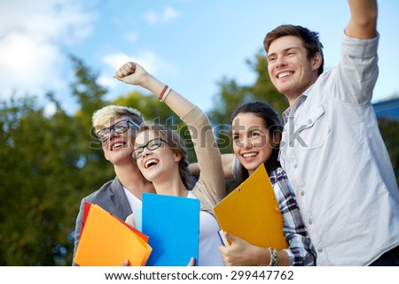education, friendship, success and teenage concept - group of happy students showing triumph gesture at campus or park - stock photo