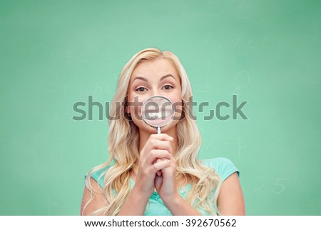 education, fun, emotions, expressions and people concept - happy smiling young woman or teenage girl having fun with magnifying glass over green school chalk board background - stock photo