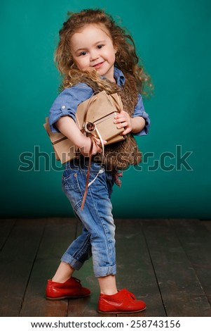 Education - funny little girl with books. Cute child in studio. Green background. Stack of books in hands - stock photo