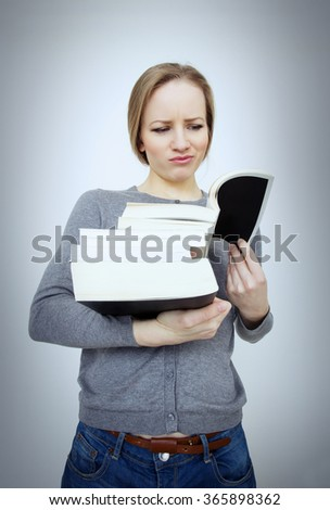 Education, graduation and people concept. Girl reading a book.Girl holding a stack of books and looks critical and disaffected