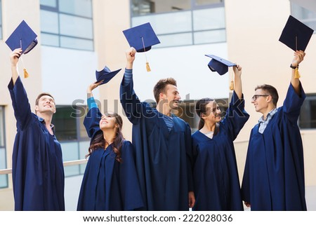 education, graduation and people concept - group of smiling students in gowns waving mortarboards outdoors - stock photo