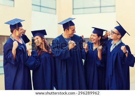 education, graduation and people concept - group of smiling students in mortarboards and gowns making triumph gesture outdoors - stock photo