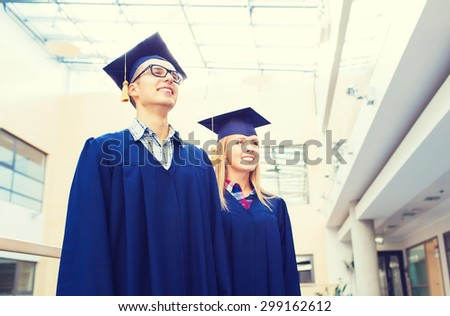 education, graduation and people concept - group of smiling students in mortarboards and gowns outdoors - stock photo