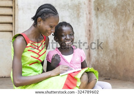 Education Happiness Symbol: African schoolgirls smiling and laughing in the streets of Bamako, whilst learning and studying for school lessons. Candid photo outside of their classroom. - stock photo