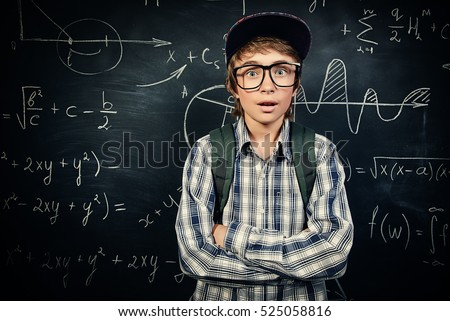 Education, high school, college. Portrait of a funny emotional student boy standing by a school blackboard.