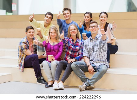 education, high school, friendship, drinks and people concept - group of smiling students with paper coffee cups showing thumbs up gesture - stock photo