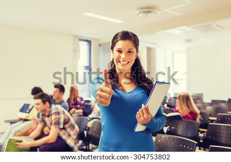 education, high school, gesture and people concept - group of smiling students with notepads showing thumbs up in lecture hall - stock photo