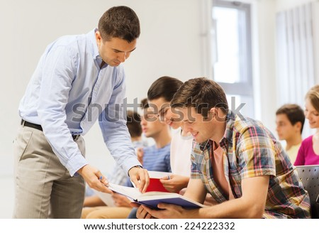 education, high school, teamwork and people concept - group of smiling students and teacher with books talking in classroom - stock photo