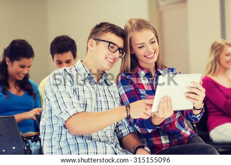 education, high school, teamwork and people concept - group of smiling students with tablet pc computers in lecture hall - stock photo