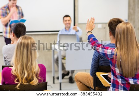education, high school, teamwork and people concept - group of students raising hand and teacher in lecture hall or classroom