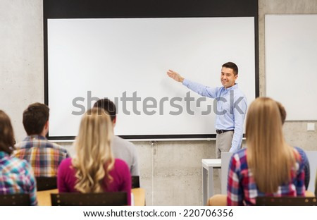 education, high school, teamwork and people concept - smiling teacher standing in front of students and showing something on white board in classroom - stock photo