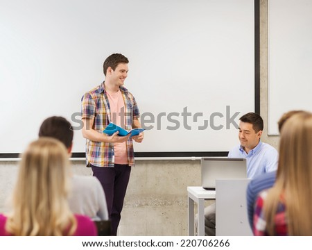 education, high school, technology and people concept - smiling student boy with notebook, laptop computer standing in front of students and teacher in classroom - stock photo
