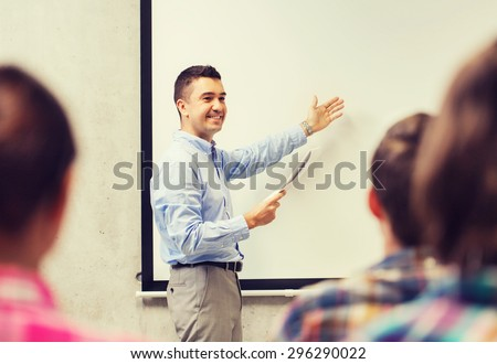 education, high school, technology and people concept - smiling teacher with notepad, laptop computer standing in front of students and showing something on white board in classroom - stock photo