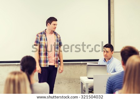 education, high school, technology and people concept - student boy standing in front of students and teacher with laptop computer in classroom - stock photo