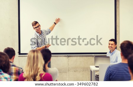 education, high school, technology and people concept - student standing with remote control, laptop computer in front of teacher and classmates in classroom - stock photo