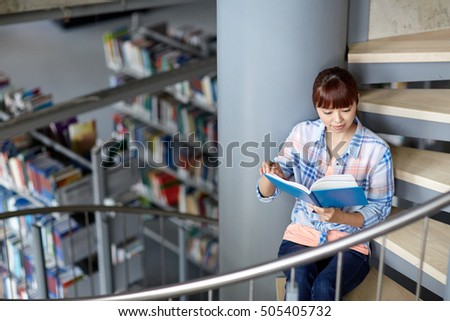 education, high school, university, learning and people concept - asian student girl reading book sitting on stairs at library