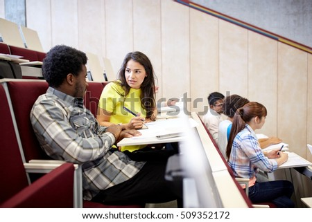 education, high school, university, learning and people concept - group of international students with notebooks talking at lecture hall