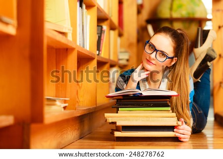 Education highschool concept. Female student charming long hair girl blue glasses working in college library with stack books. Indoor - stock photo
