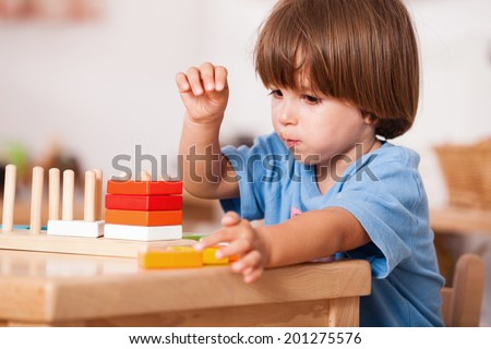 Education image from a kindergarten: Child playing with his toys at the table - stock photo