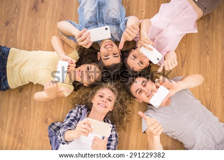 Education, people and technology concept - close up of students or friends with smartphones lying on floor in circle. - stock photo