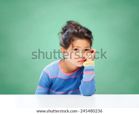 education, people, childhood and emotions concept - sad or bored little school girl over green chalk board background - stock photo