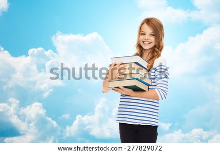 education, people, children and school concept - happy little student girl with many books over blue sky with clouds background - stock photo
