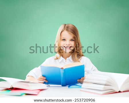 education, people, children and school concept - happy student girl reading book at school over green chalk board background - stock photo
