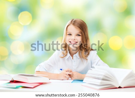 education, people, children and school concept - happy student girl sitting at table with books and writing in notebook over green lights background - stock photo