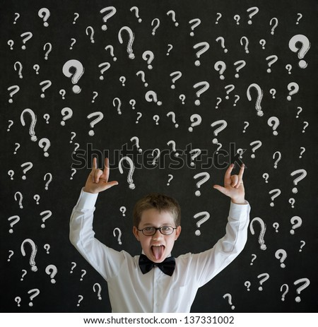 Education rocks boy dressed up as business man with chalk questions marks on blackboard background - stock photo