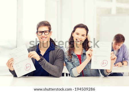 education, school and people concept - two teenagers holding test or exam with grade A - stock photo