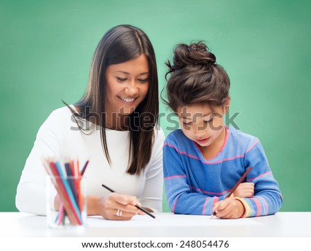 education, school, children, creativity and happy people concept - happy teacher and girl drawing over green chalk board background