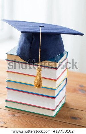 education, school, graduation and knowledge concept - close up of books and mortarboard on wooden table - stock photo