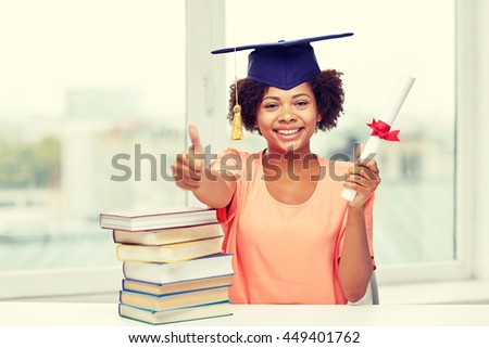 education, school, graduation, gesture and people concept - happy smiling african american student girl in bachelor cap with books and diploma sitting at table and showing thumbs up at home - stock photo